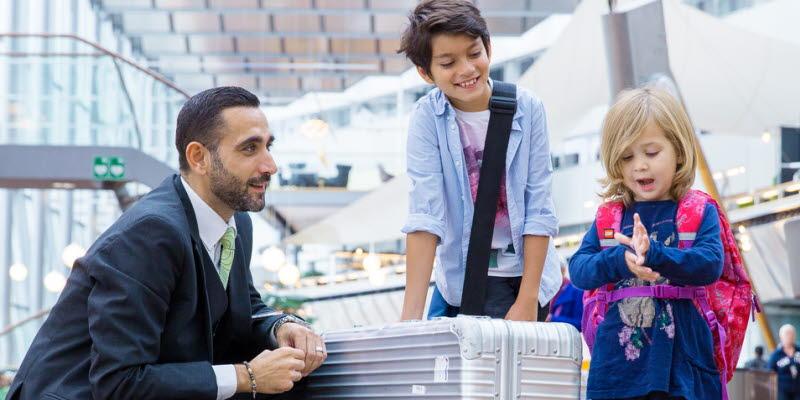 Man med två barn och silverfärgad resväska