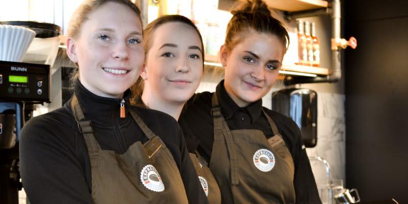 tre tjejer poserar bakom disken på Espresso house i Sky city